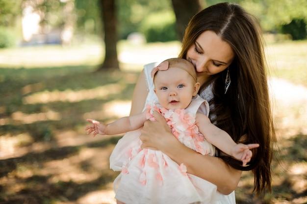 Mãe feliz, segurando sua filha nas mãos no parque verde