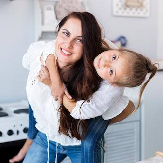 Mãe feliz, segurando sua menina adorável