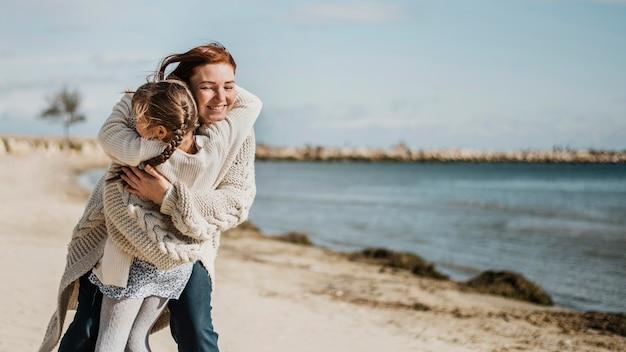 Mãe feliz segurando uma garota de tiro médio