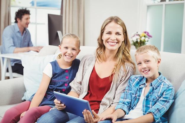 Mãe feliz sentada com as crianças no sofá
