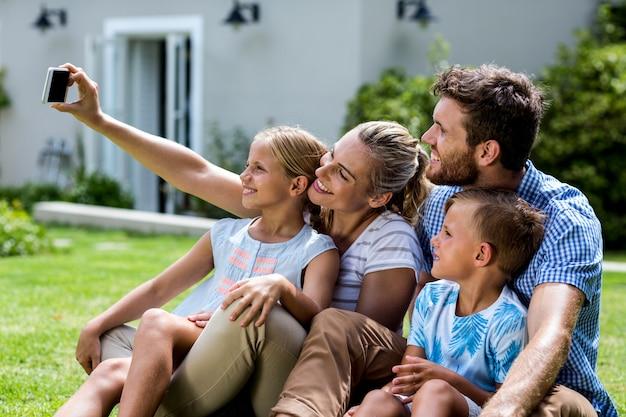 Mãe feliz tomando selfie com a família no quintal
