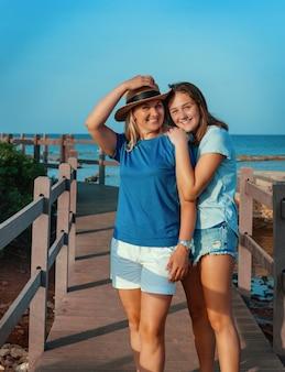 Mãe feliz usando chapéu de palha e filha adolescente em pé no cais no mar