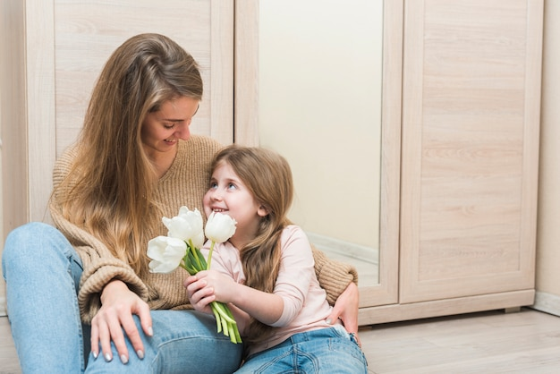 Mãe filha abraça com flores tulipa branca