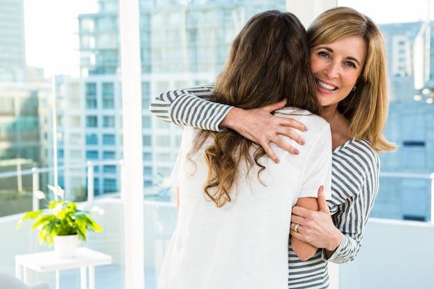 Mãe filha, abraçando, casa