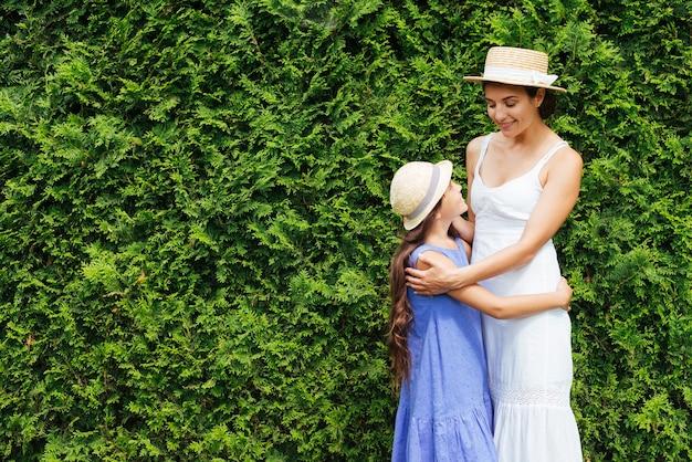 Mãe filha, abraçando, frente, arbustos