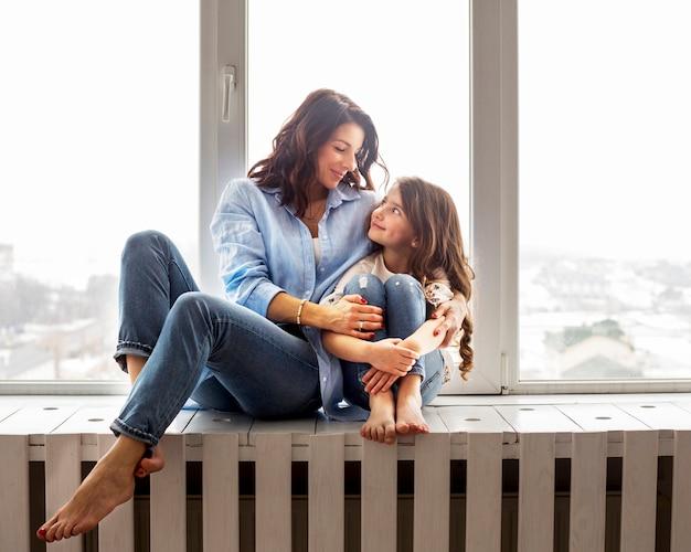 Mãe filha, abraçando, ligado, peitoril janela