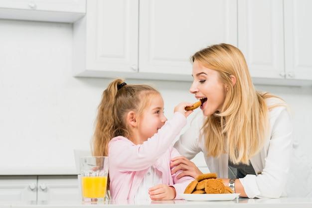 Mãe filha, com, biscoitos suco