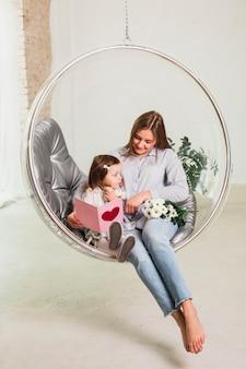 Mãe filha, com, cartão cumprimento, em, cadeira suspensa