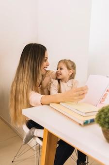 Mãe filha, com, livro, olhando um ao outro