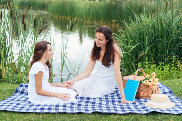Mãe filha, desfrutando, piquenique, por, a, lago