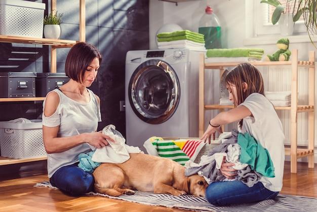 Mãe, filha e cachorro conversando e escolhendo roupas no chão