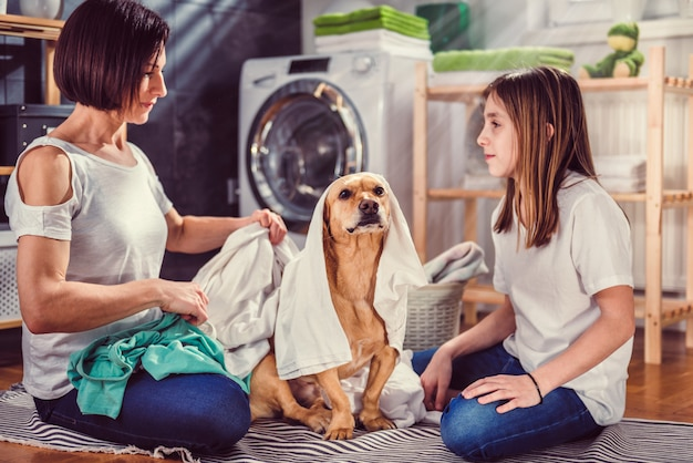 Mãe, filha e cachorro se divertindo na lavanderia