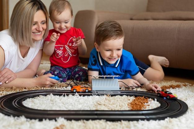 Mãe, filha e filho brincam de corrida no tapete.