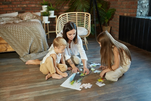 Mãe, filha e filho montam o quebra-cabeça no chão