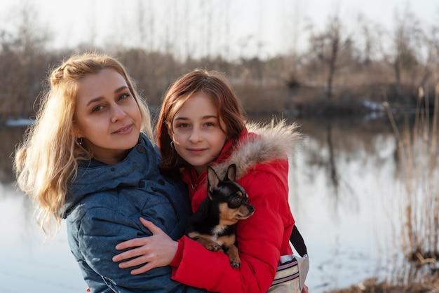 Mãe, filha e seu cachorro chihuahua de estimação em seus braços. amor aos animais. valores de família.