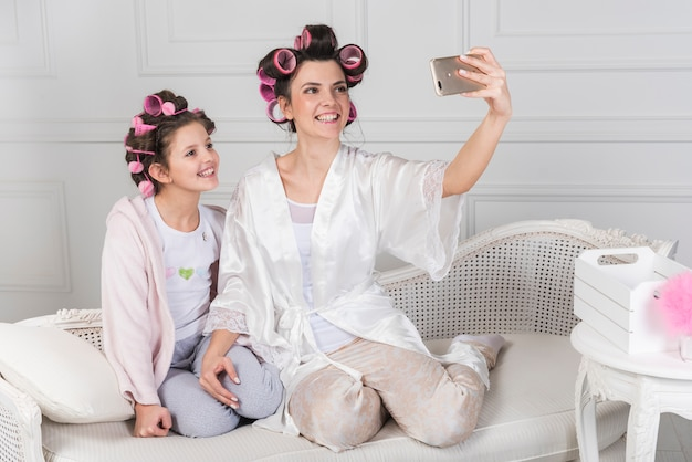 Mãe filha, em, curlers, levando, selfie