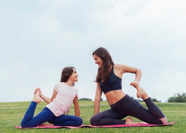 Mãe filha, fazendo, exercícios, ao ar livre