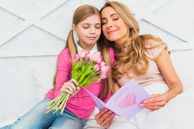 Mãe filha, sentando, com, flores, e, cartão cumprimento