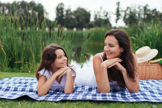 Mãe filha, sorrindo um ao outro, ao ar livre