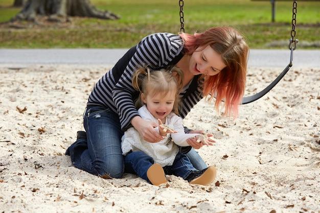 Mãe filha, tocando, com, areia, parque