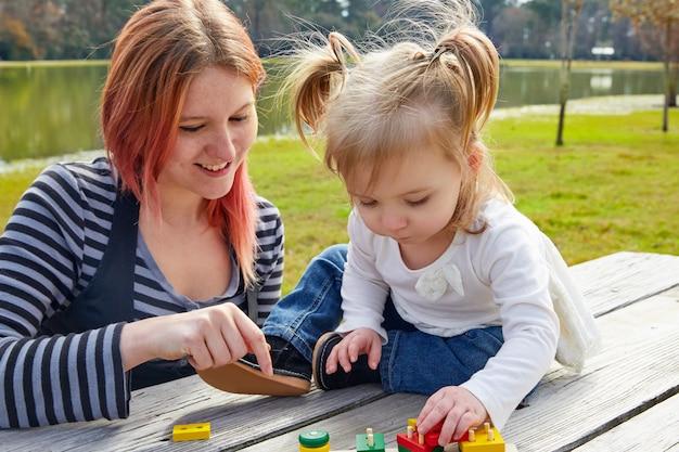 Mãe filha, tocando, com, formas, parque
