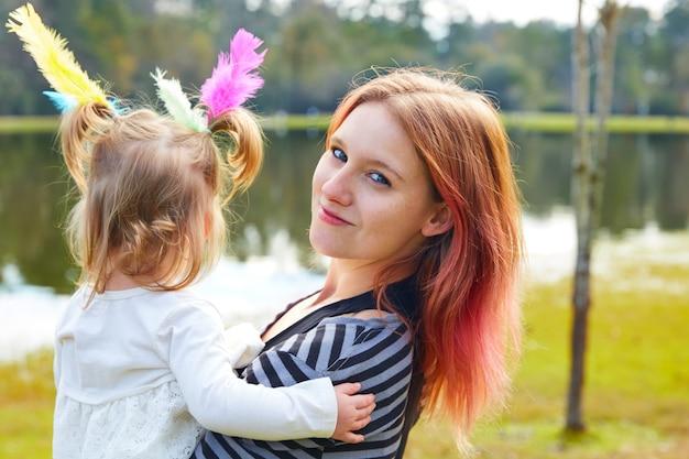 Mãe filha, tocando, com, penas, parque