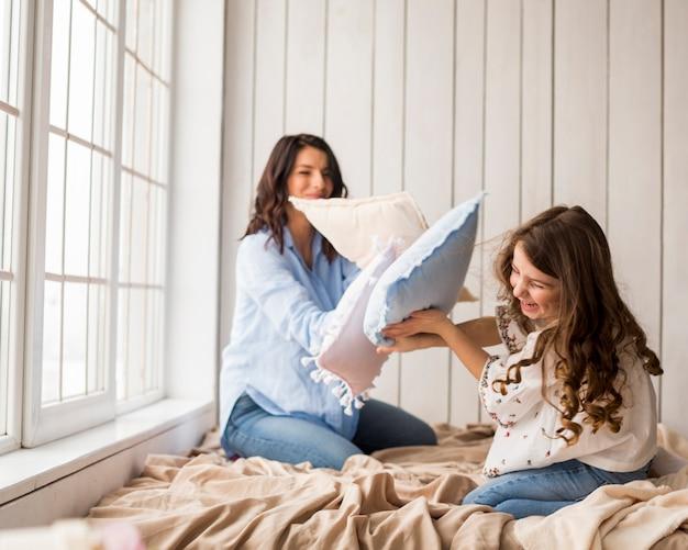 Mãe filha, tocando, com, travesseiros