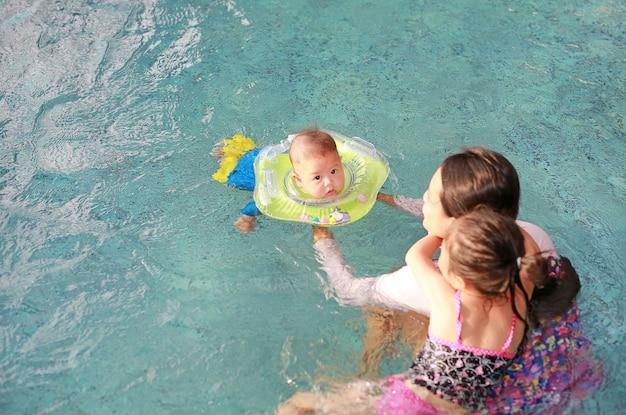 Mãe filha, treinamento, para, criança bebê, flutuante, em, piscina, com, segurança, por, bebê, pescoço, flo