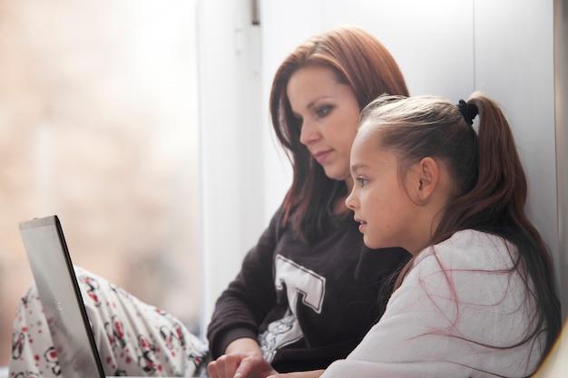 Mãe filha, usando computador portátil