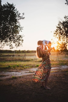 Mãe filho, abraçando, em, a, pôr do sol