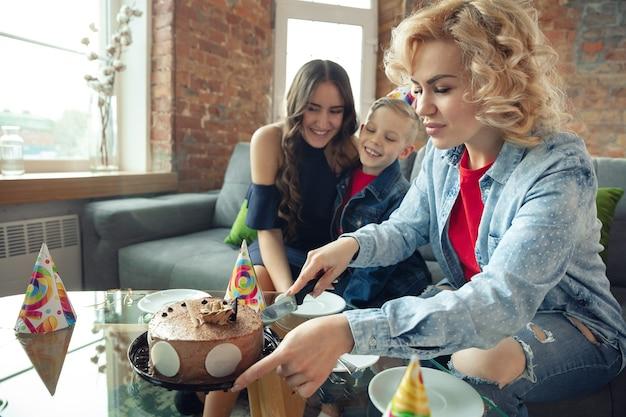 Mãe, filho e irmã em casa se divertindo, conforto e aconchego comemorando aniversário