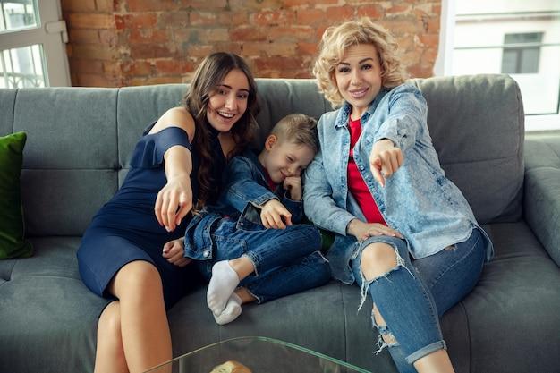 Mãe, filho e irmã em casa se divertindo