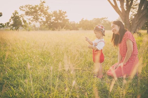 Mãe, filho, tocando, capim, campos, ao ar livre, à noite