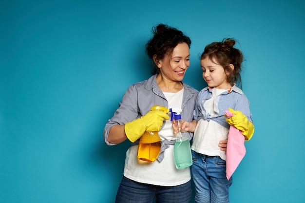Mãe fofa abraça suavemente sua filha e sorri enquanto posa com detergentes em mãos em uma superfície azul com espaço de cópia