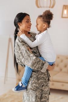 Mãe forte e amorosa entusiasmada conversando com sua filha e segurando-a