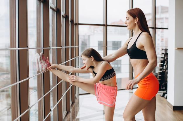 Mãe forte e filha filha estão envolvidos em fitness, exercício e alongamento no ginásio