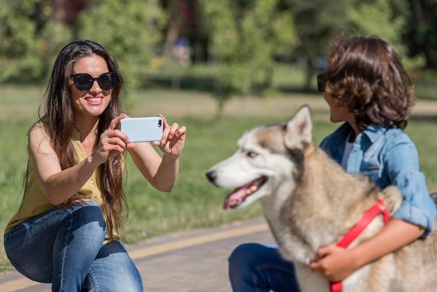 Mãe fotografando filho com cachorro no parque
