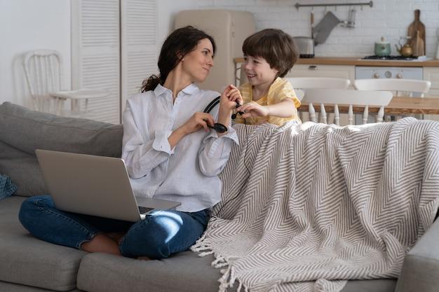 Mãe freelancer sentada no sofá em casa, trabalhando no laptop, criança distraída e pedindo atenção