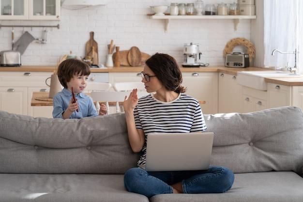 Mãe freelancer trabalhando no laptop em casa durante o bloqueio, criança barulhenta distrai pedindo atenção.