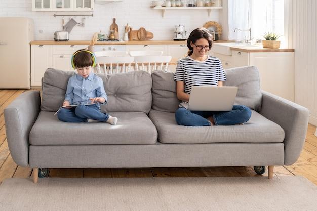 Mãe freelancer trabalhando remoto do escritório em casa no laptop, sentada no sofá, criança brincando no tablet