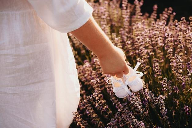 Mãe gorducha segurando um par de sapatos de bebê e caminhando em um campo de lavanda com um lindo vestido branco