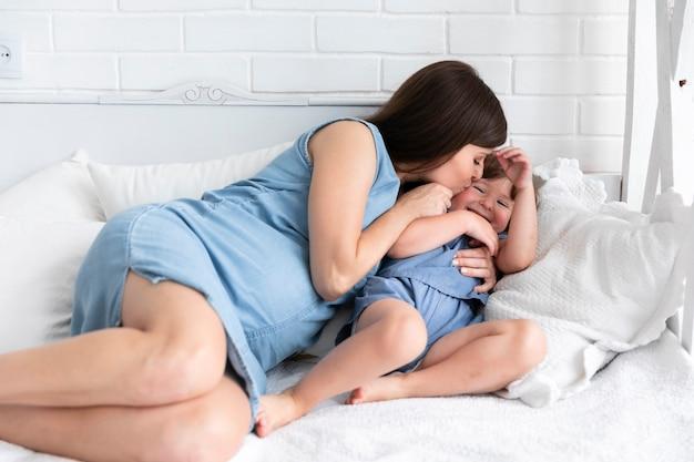Mãe grávida beijando a filha dela