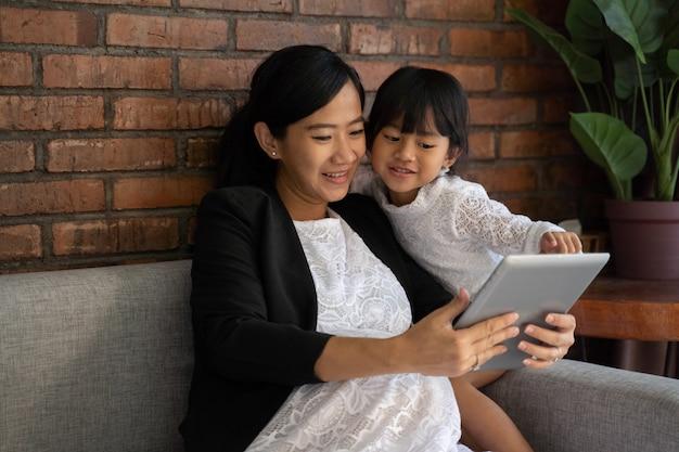 Mãe grávida com a filha sentada no sofá gosta de usar tablet