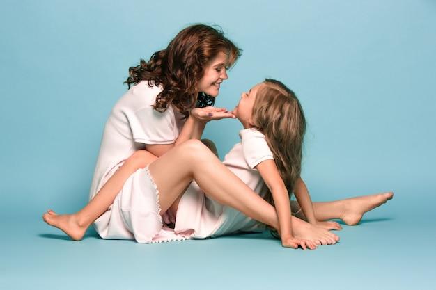 Mãe grávida com filha adolescente. retrato de estúdio de família