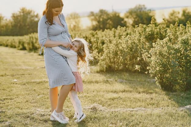 Mãe grávida com sua filha em um campo