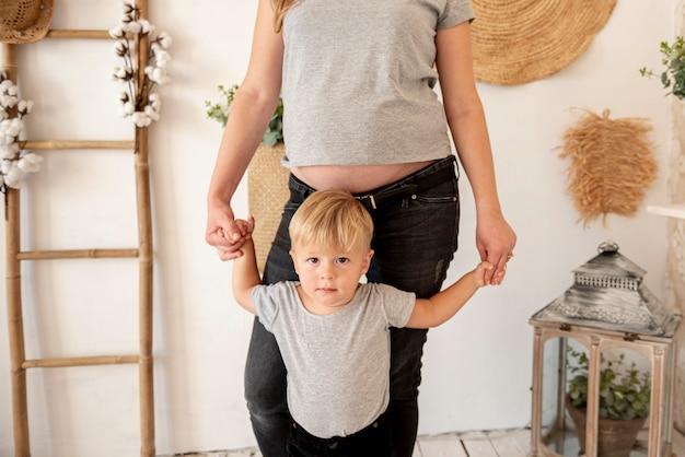 Mãe grávida de close-up, segurando seu filho