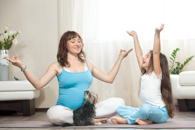 Mãe grávida e criança pequena meditando em casa