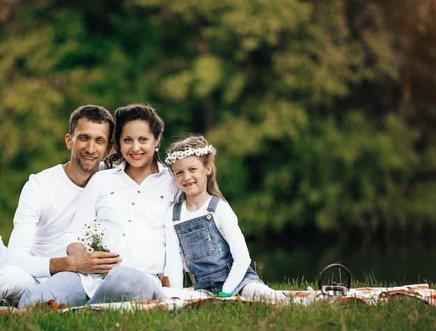 Mãe grávida e feliz pai e filha em um piquenique no parque em um dia ensolarado. a foto tem um espaço vazio para o seu texto