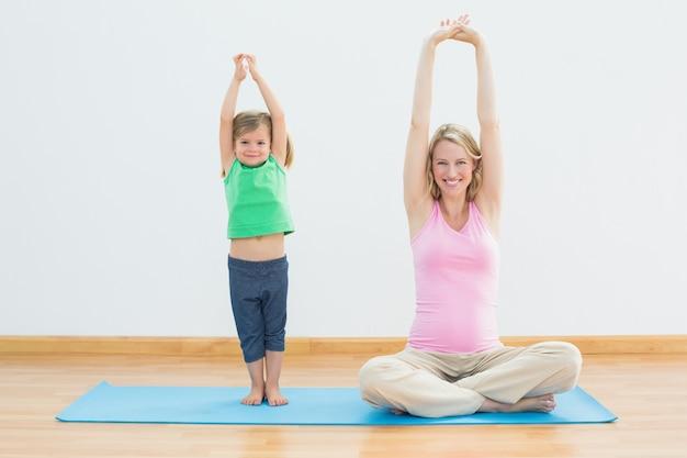 Mãe grávida e filha fazendo ioga juntos