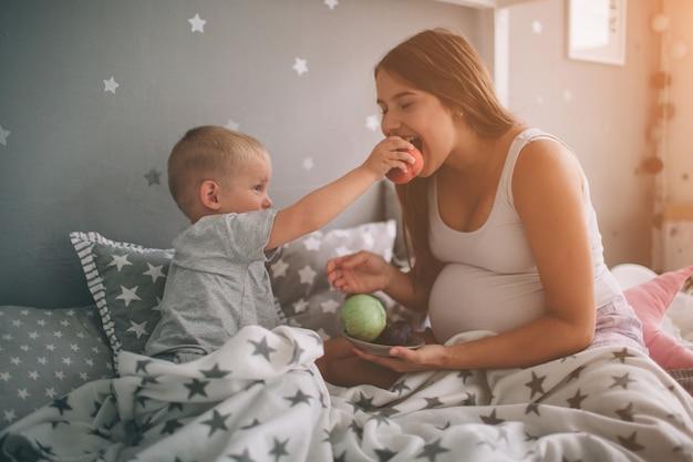 Mãe grávida e filho pequeno menino estão comendo uma maçã e pêssego na cama t em casa pela manhã. estilo de vida casual no quarto.